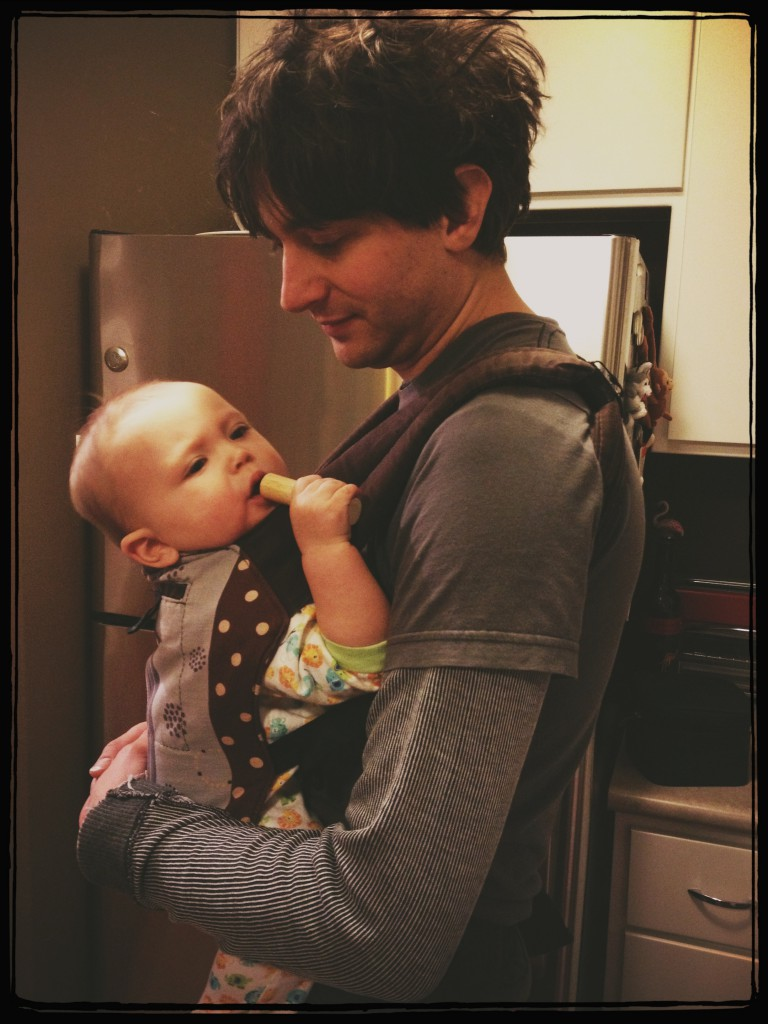 Henrie holding Felix in a baby carrier