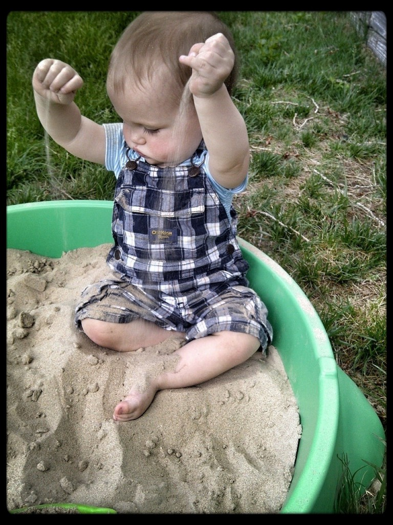letting the sand fall between his little fingers