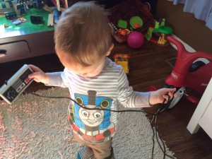 holding the NES controller in one hand, cord in the other