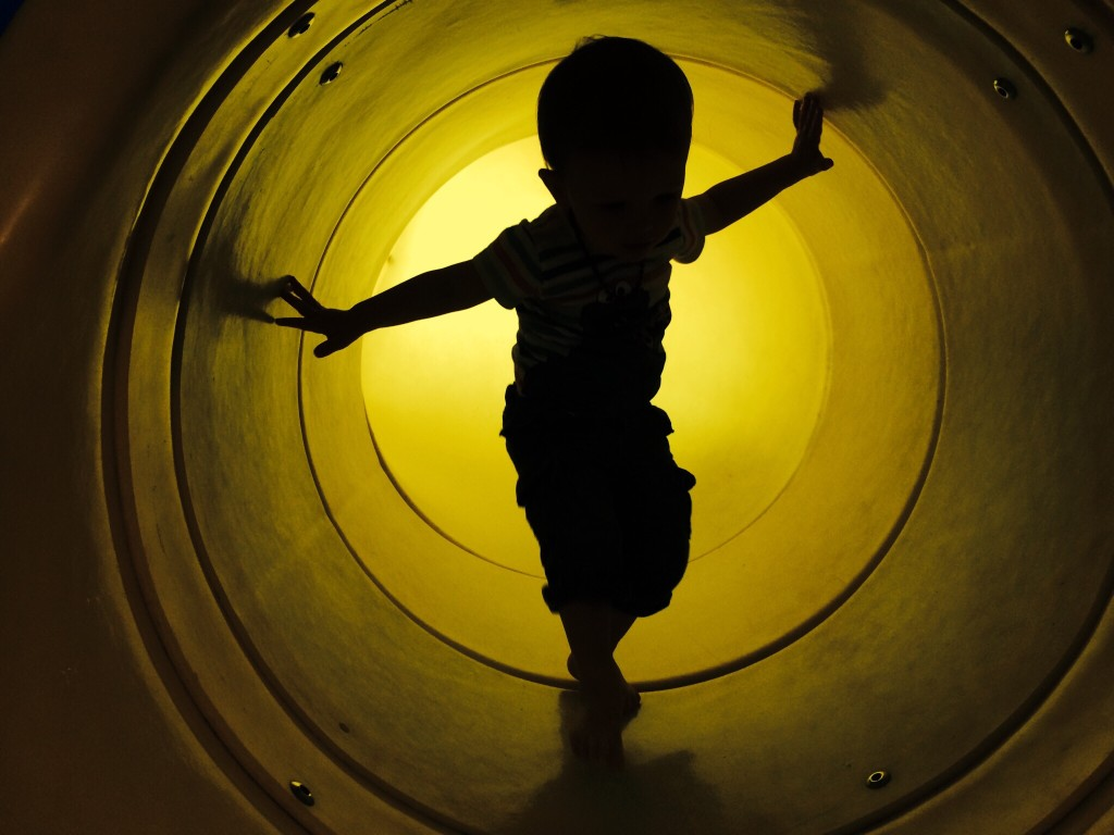 Felix plays in a yellow play tube