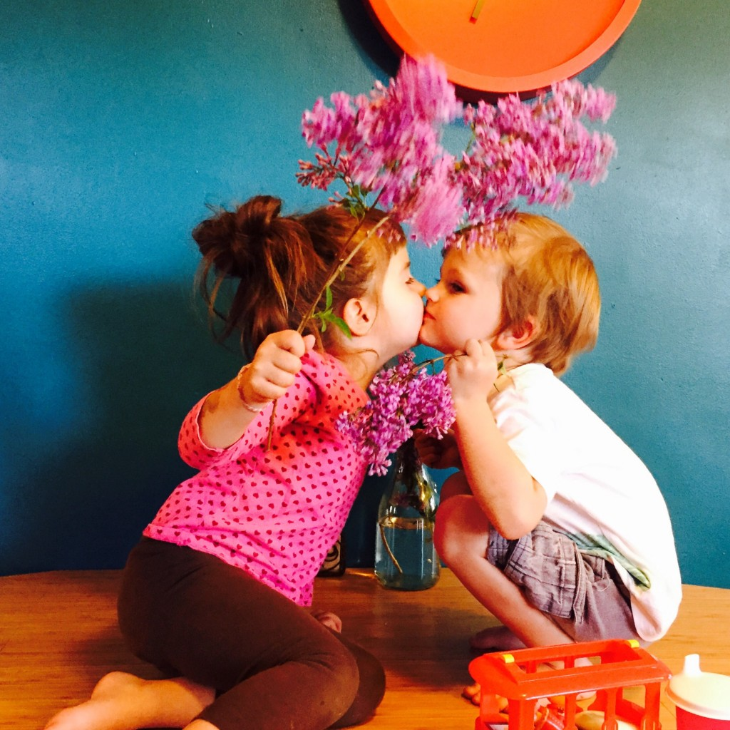 Felix and Stella kiss holding lilacs